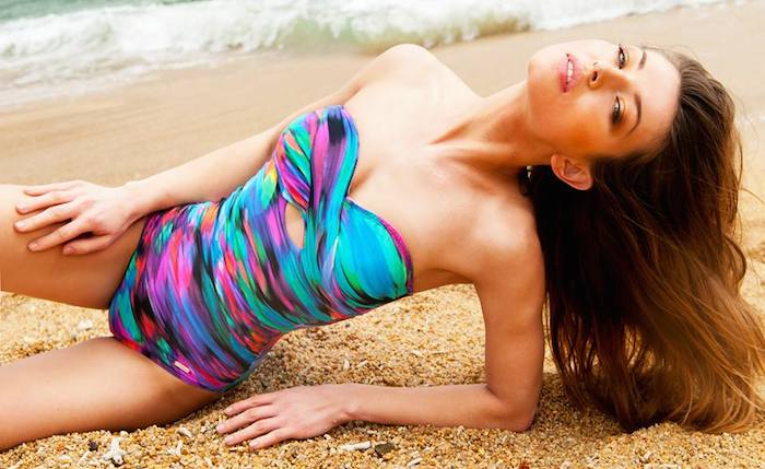 Model lying in sand on the beach wearing a rainbow colour swimsuite