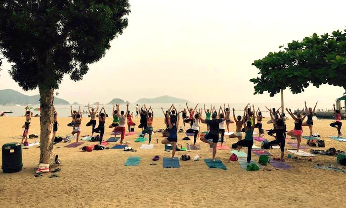 a group of people doing yoga on the beach in hong kong