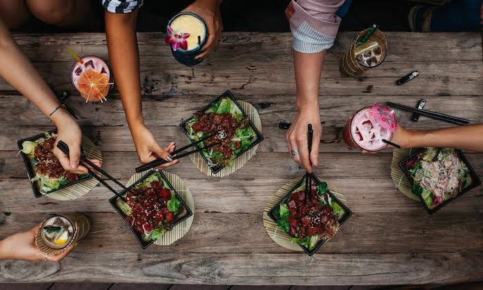 group of friends sharing cocktails and poke bowls