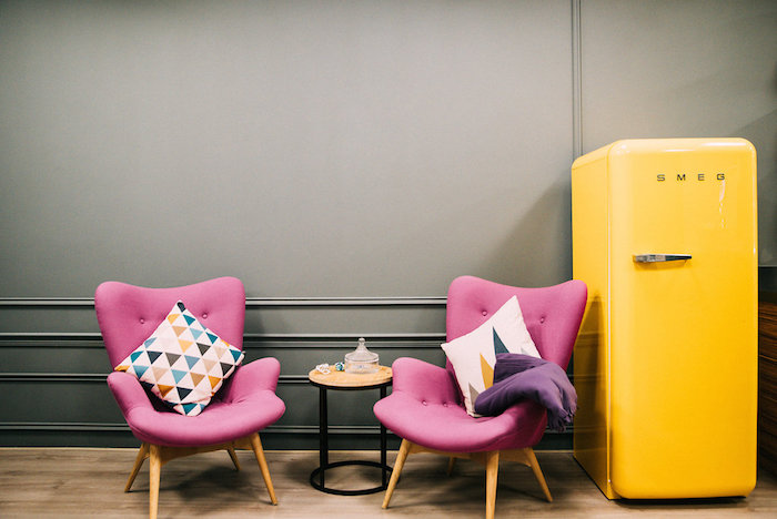 Pink chairs and a yellow SMEG fridge in a pantry